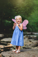 Little girl with fairy wings in the forest