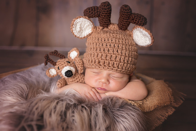 Newborn baby boy deer with stuffed deer
